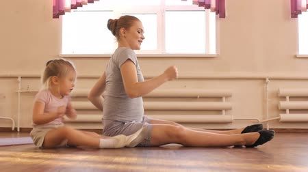 gimnastyka : Pregnant woman with her first kid daughter doing gymnastics