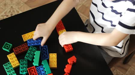bloklar : boy playing with lots of colorful plastic blocks indoor