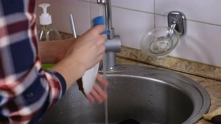 trabalhos domésticos : Woman washes a saucer and catches the glass falling into the sink. Vídeos