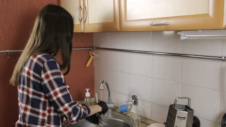 csempe : Brunette with long hair in a plaid shirt in rubber gloves wash the glass and saucer. Stock mozgókép