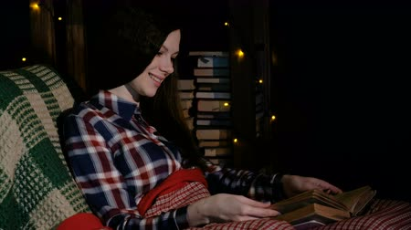 читатель : Butiful woman under the blanket on the couch reading a book and flips through the pages Стоковые видеозаписи