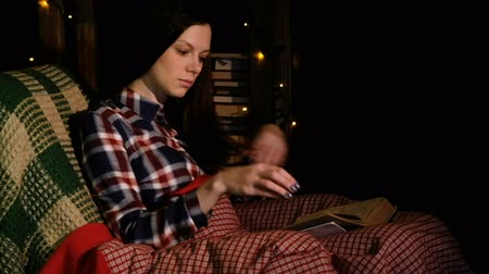 портретный : Butiful woman under the blanket on the couch reading a book and flips through the pages Стоковые видеозаписи