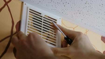 conditioner : Male hand tightening the screws with a screwdriver on the grate vents home. Close up 4K.
