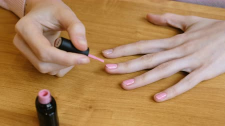 cuidadoso : Close up of a young woman whoCloseup of young woman doing her nails. Lacquered nails color pink. 4K