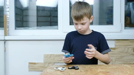 camera rotation : Little child playing with modern popular hand toy - spinner. Spinner hypnotizing boy. 4K