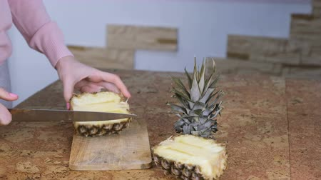chop up : Woman is cuting the pineapple on a cutting board. Hands closeup. High speed video.
