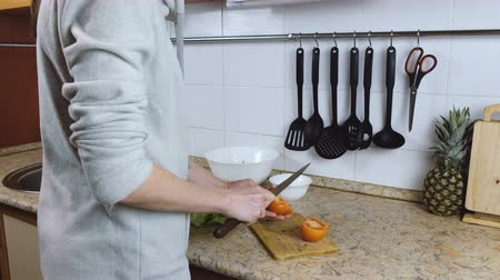 pepinos : Unrecognizable woman cuts tomatoes on a cutting board on a kitchen table. Hands close up. Vídeos