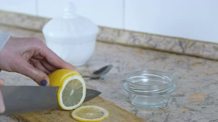 yarım uzunluk : Close-up of woman hand cutting lemon on wood cutting board in the kitchen. Stok Video