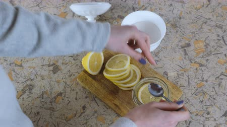 cítrico : Close-up of woman hand folds slices of lemon into a jar and sprinkles them with sugar with a spoon.