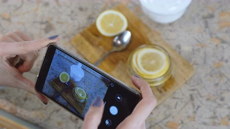 cítrico : Close-up of woman hand with phone making photo slices of lemon in jar.