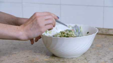 cucumber : Close-up of woman hand mixes vegetable salad in a white plate on the kitchen table. Side view. Slomo