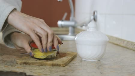 cítrico : Close-up of woman hand closes the jar with slices of lemon with red lid. Vídeos