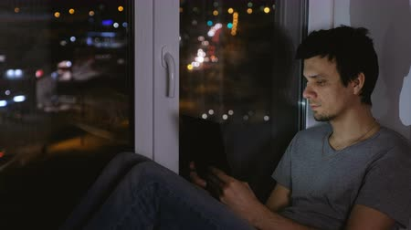 utca : Man sitting on the windowsill in the dark night and looking at street. Using tablet for web.