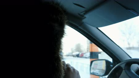 incompleto : Unrecognizable man in a fur hood smokes an electronic cigarette in the car.