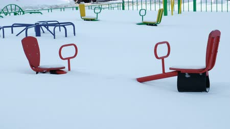 dalgalanan : Childrens Playground with seesaw and carousels in the snow in winter. The camera is static.