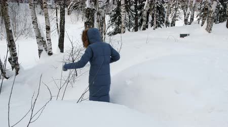 kar fırtınası : Unrecognizable woman in blue hooded jacket descends from the mountain on snowy path and falls.