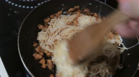 související : Close-up of a mans hand mixes with a wooden spatula spaghetti, minced meat and egg in a pan
