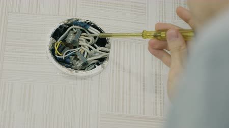 heat resistant : Man worker open the lid of electrical junction box and repairing the wires with screwdriver.