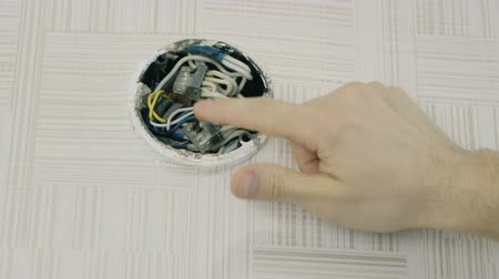 подключение : Close-up mans hands repairing the wires on electrical junction box with screwdriver. Open the lid