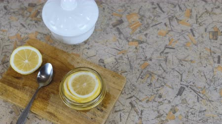 cítrico : Close-up lemon slices in jar, spoon, half lemon, sugar bowl on cutting board and kitchen table.