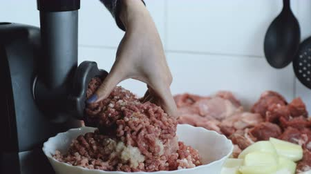 фарш : Close-up beef and pork meat and onion through electric meat mincer at home.