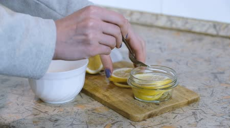 cítrico : Close-up of woman hand folds slices of lemon into a jar and sprinkles with sugar with a spoon. Slomo Vídeos