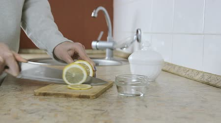 cítrico : Close-up of woman hands cutting lemon on wood cutting board in the kitchen. Side view.