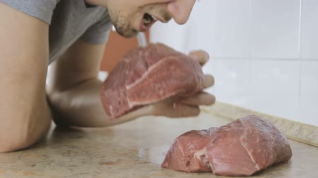 sirloin : Man bites off a piece of raw beef and chews it. Eskimo is eating uncooked beef meat