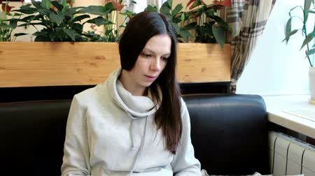 selecionando : Brunette young woman in a light jacket reads and flips through the menu sitting in a cafe. Close-up. Vídeos