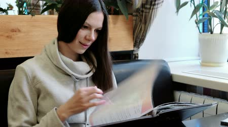 поздний завтрак : Brunette young woman in a light jacket reads and flips through the menu sitting in a cafe. Стоковые видеозаписи