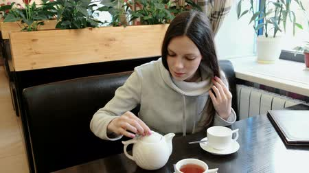 porcelana : Woman brunette opens the teapot, sniffs it and pours tea from a kettle into a cup.