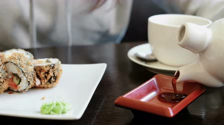 garnélarák : Womans hand pours soy sauce in small rectangular plate, rolls and cup of tea on background. Stock mozgókép