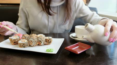 california rolls : Unrecognizable girl pours soy sauce in small rectangular plate, rolls and cup of tea on background.