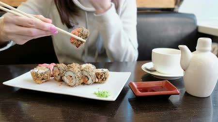 california rolls : Woman takes roll from soy sauce by wood sticks bites it and chews. Close-up view.