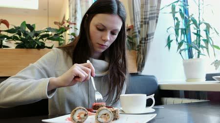 tempura : Brunette girl eats rolls with a fork in a cafe. Front view. Stock Footage