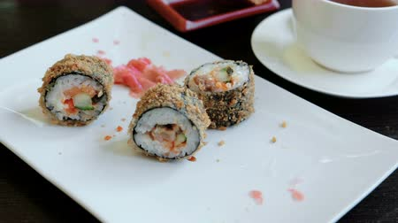 california rolls : Rolls on a white square plate on a wooden table. Top view.
