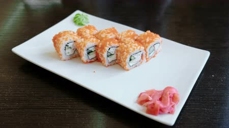 california rolls : Rolls with caviar with pickled ginger and wasabi on a white rectangular plate.