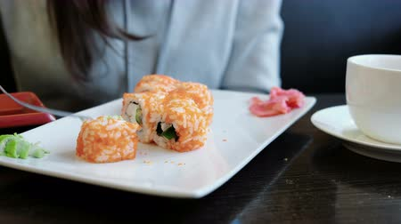california rolls : Close-up womans hands put wasabi and ginger on the roll with a fork and dip the roll in soy sauce. Stock Footage