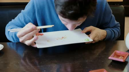 travessura : Young man brunette eats the crumbs from the plate and licks the plate with tongue. Front view.