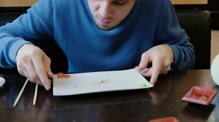travessura : Young man brunette in blue sweater eats the crumbs from the plate and licks the plate with tongue.