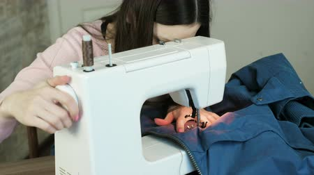 zíper : Young woman sews blue jacket on white sewing mashine.