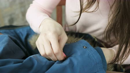 zíper : Close-up of a womans hand sew a leather insert to a blue jacket by hand.