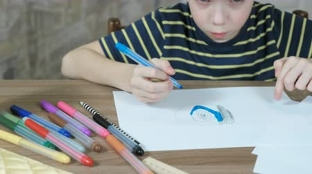 yetenekli : Boy of 7 years paint his paint the picture with a blue felt pen on white paper.