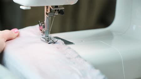 labour : Close-up womans hands sewing fabric on sewing machine. Slow motion. Stock Footage