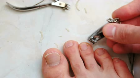 csipesz : Man cutting toenails with clipper. Male cut toenails on foot. Foot and toes close-up. Top view.