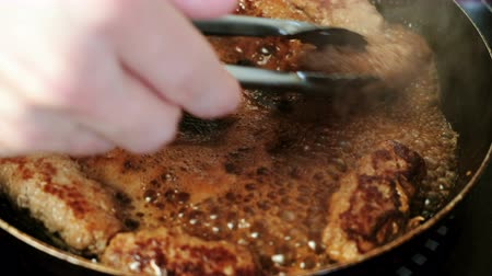 útil : Mens hands with metal tongs turn around fried cutlets in a pan. Close-up view.