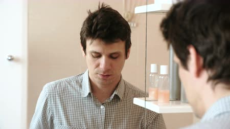 bigode : Man shaves while looking in the mirror. Brunette in a plaid light shirt. Stock Footage