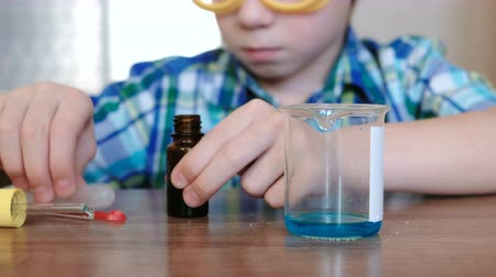 pipette : Experiments on chemistry at home. Boy pours blue liquid from a jar into a beaker with a pipette.