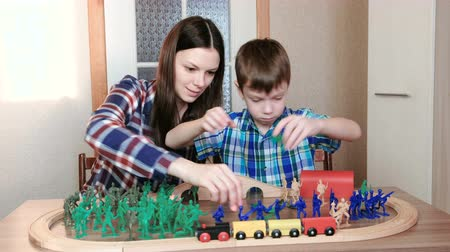 train tunnel : Playing together. Mom and son are playing a wooden railway with train, wagons and tunnel with plastic soldiers sitting at the table.