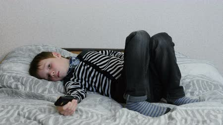 наслаждаясь : Watching TV lying on the couch. Upset boy is watching TV and switches the channels.